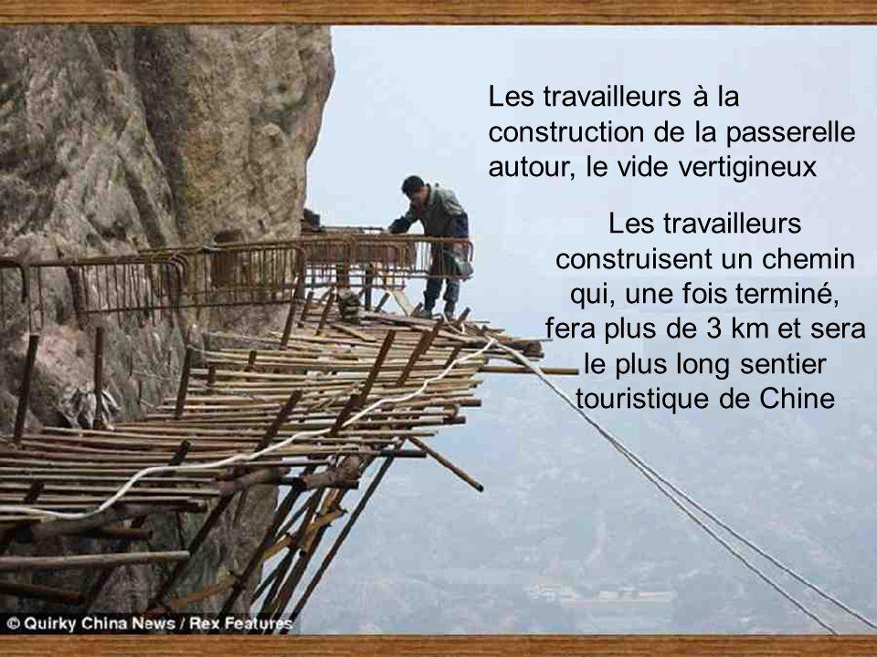 Les travailleurs à la construction de la passerelle autour, le vide vertigineux Les travailleurs construisent un chemin qui, une fois terminé, fera plus de 3 km et sera le plus long sentier touristique de Chine