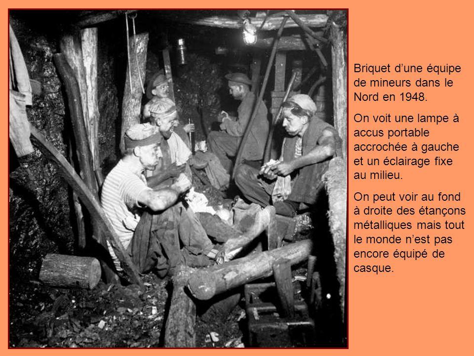Boiseur dans le Nord en 1948 en train de confectionner une gorge de loup, éclairé par sa lampe à accus posée au sol devant lui.