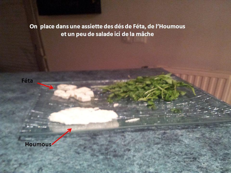 On place dans une assiette des dés de Féta, de lHoumous et un peu de salade ici de la mâche Féta Houmous
