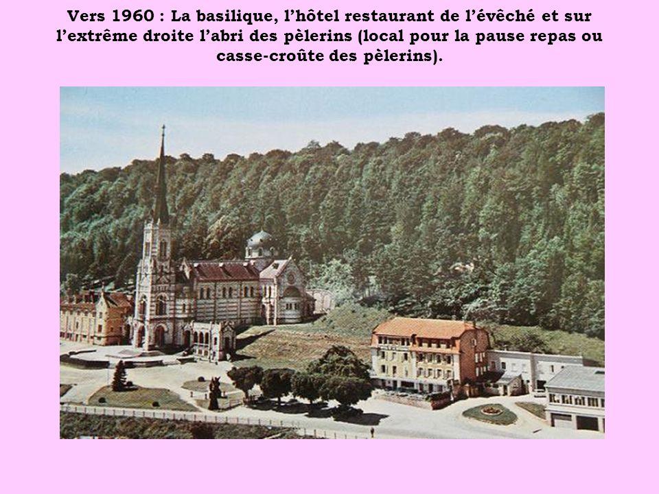 Vers 1960 : La basilique, lhôtel restaurant de lévêché et sur lextrême droite labri des pèlerins (local pour la pause repas ou casse-croûte des pèleri