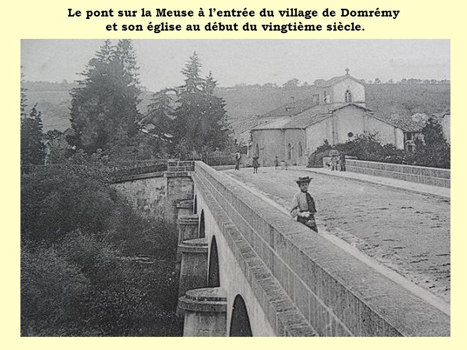 Le pont sur la Meuse à lentrée du village de Domrémy et son église au début du vingtième siècle.