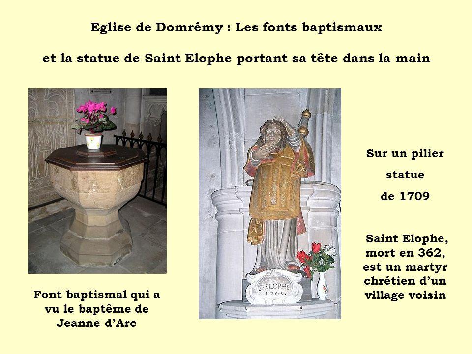 Eglise de Domrémy : Les fonts baptismaux et la statue de Saint Elophe portant sa tête dans la main Sur un pilier statue de 1709 Saint Elophe, mort en