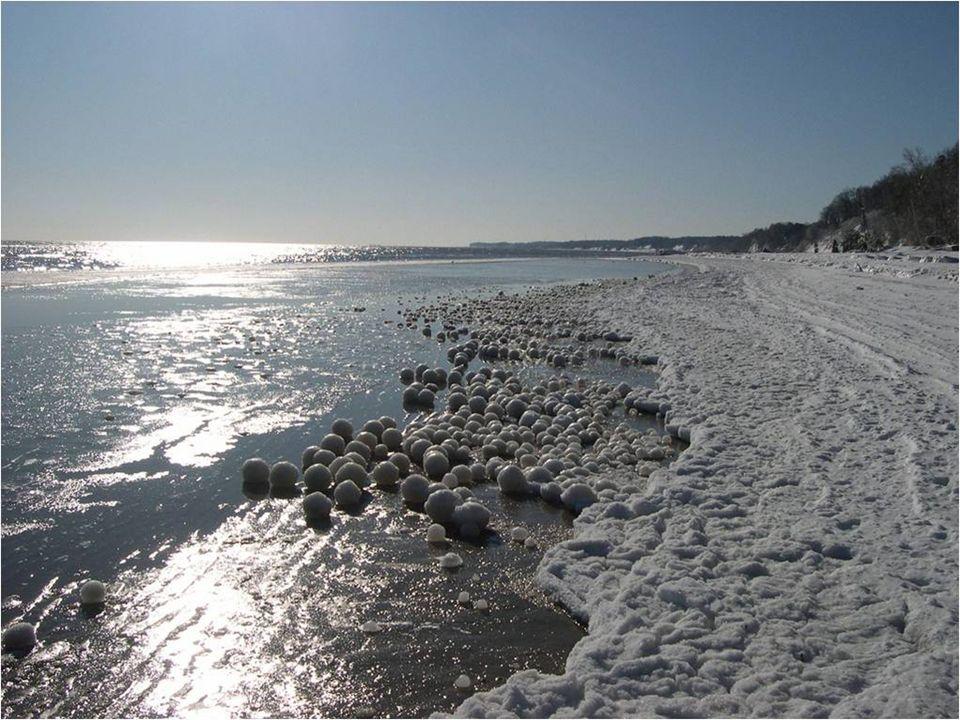 Des centaines, des milliers de boules de glace avec le coeur de neige et de la taille d'un ballon de football s'accumulent le long du bord dans un spe