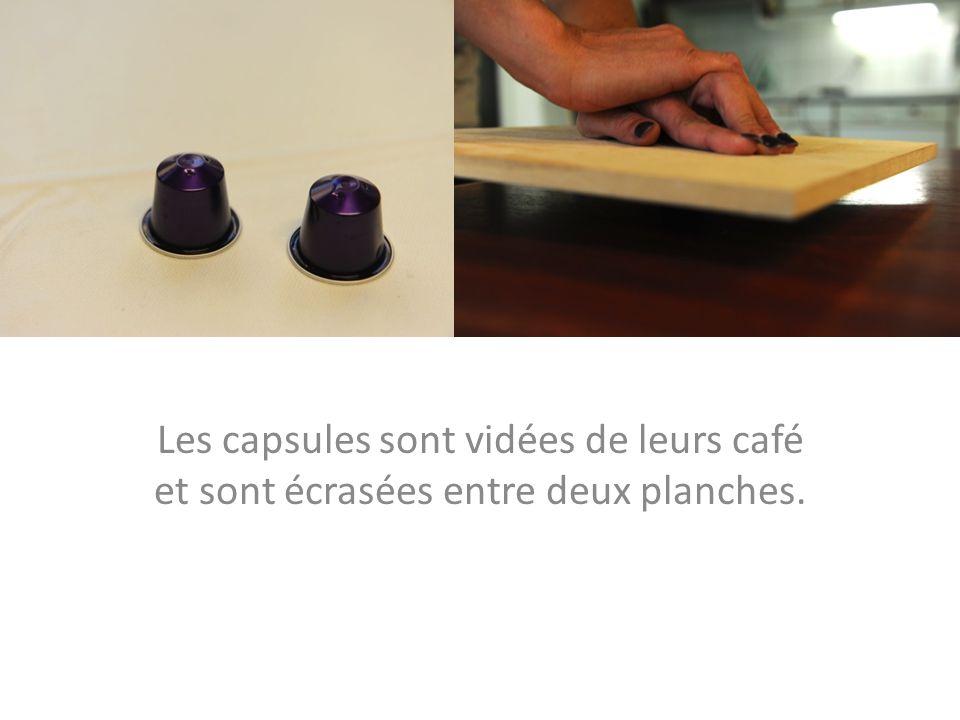Les capsules sont vidées de leurs café et sont écrasées entre deux planches.
