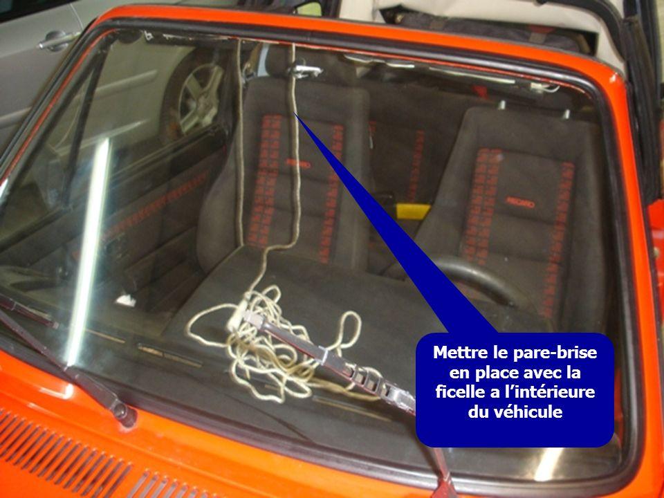 Mettre le pare-brise en place avec la ficelle a lintérieure du véhicule