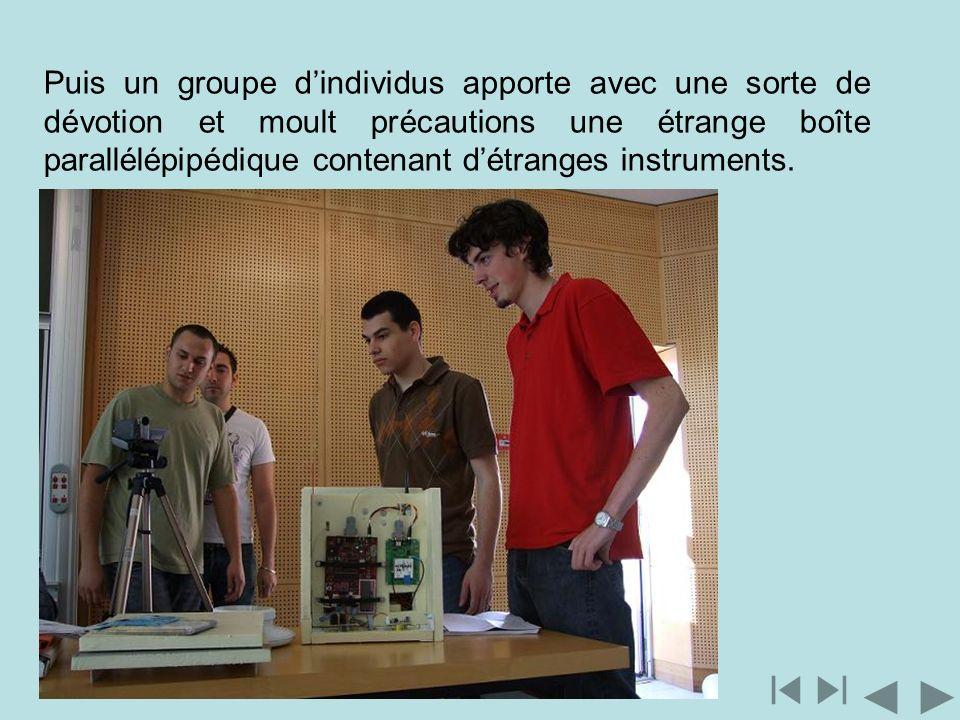 Puis un groupe dindividus apporte avec une sorte de dévotion et moult précautions une étrange boîte parallélépipédique contenant détranges instruments