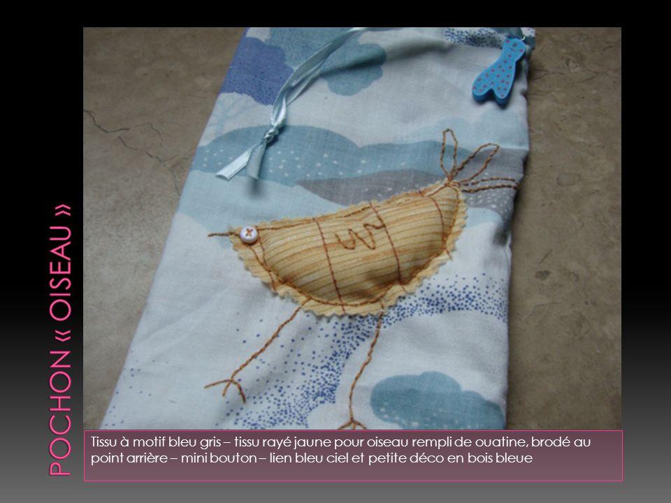 Tissu à motif bébé – les motifs sont rebrodés ton sur ton sur leur pourtour - lien bleu ciel et perle en bois bleue