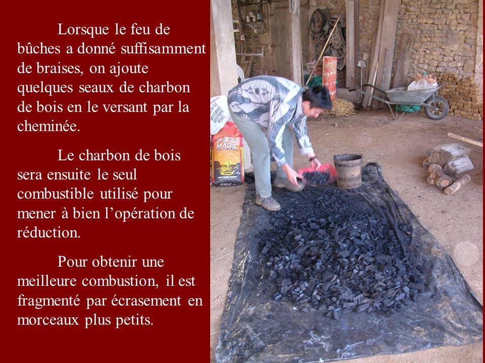 Lorsque le feu de bûches a donné suffisamment de braises, on ajoute quelques seaux de charbon de bois en le versant par la cheminée.