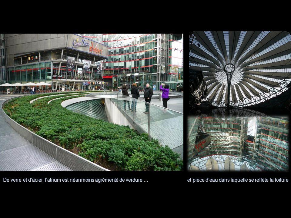 et pièce deau dans laquelle se reflète la toitureDe verre et dacier, latrium est néanmoins agrémenté de verdure …