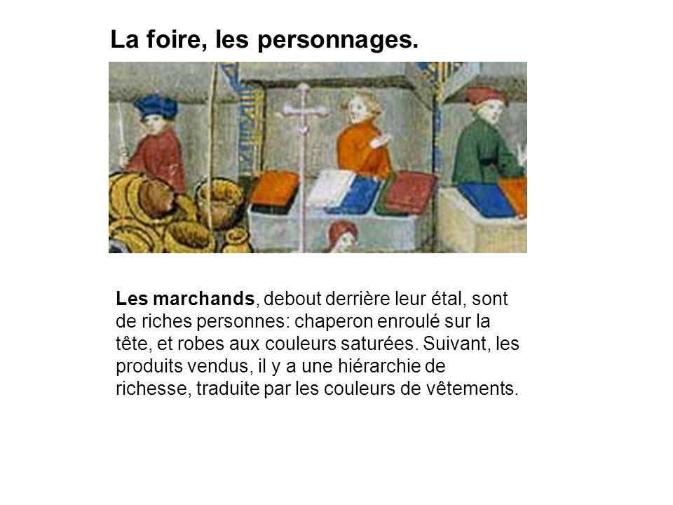 La foire, les personnages. Les marchands, debout derrière leur étal, sont de riches personnes: chaperon enroulé sur la tête, et robes aux couleurs sat