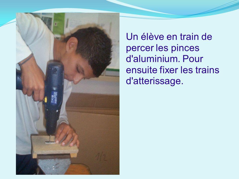 Un élève en train de percer les pinces d'aluminium. Pour ensuite fixer les trains d'atterissage.