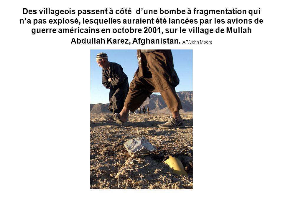 Des villageois passent à côté dune bombe à fragmentation qui na pas explosé, lesquelles auraient été lancées par les avions de guerre américains en octobre 2001, sur le village de Mullah Abdullah Karez, Afghanistan.