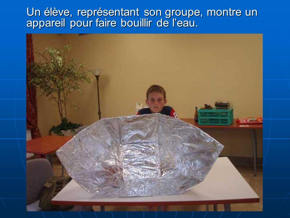 Un élève, représentant son groupe, montre un appareil pour faire bouillir de leau.