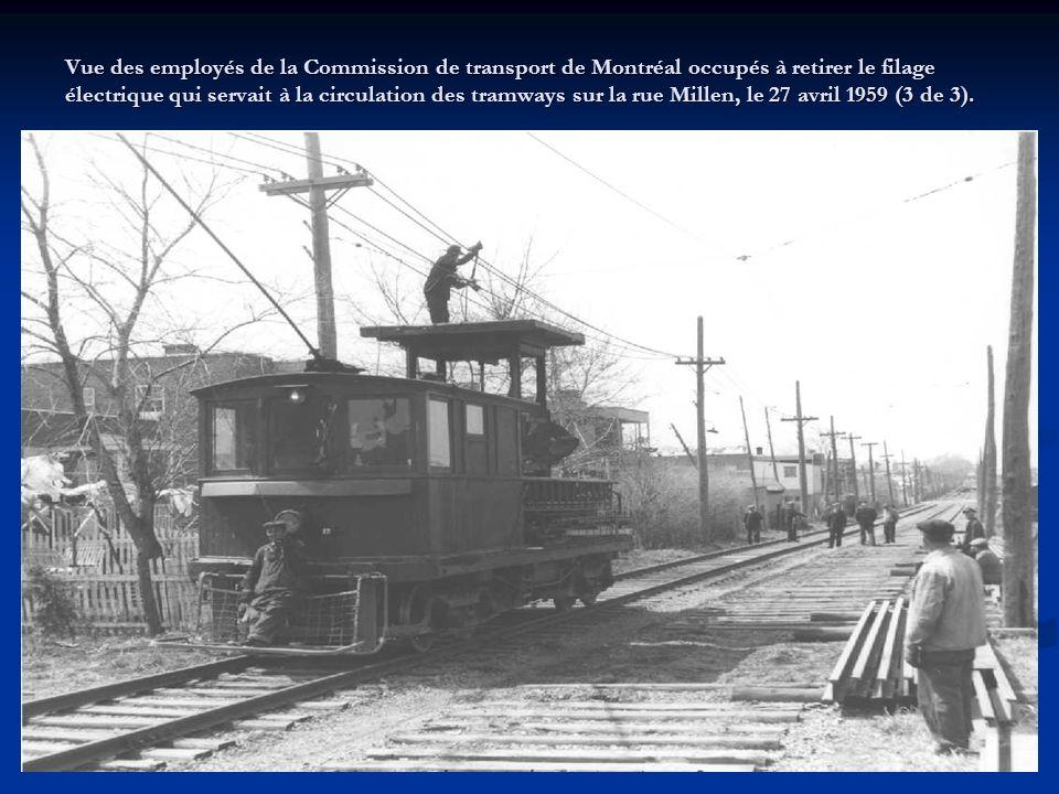 Vue des employés de la Commission de transport de Montréal occupés à retirer les voies qui servaient à la circulation des tramways sur la rue Millen,
