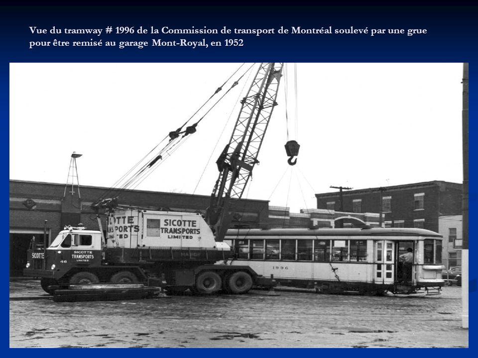 Vue de plusieurs employés de la Commission de transport de Montréal effectuant des travaux de restauration des voies sur la rue Saint-Laurent, à l'int