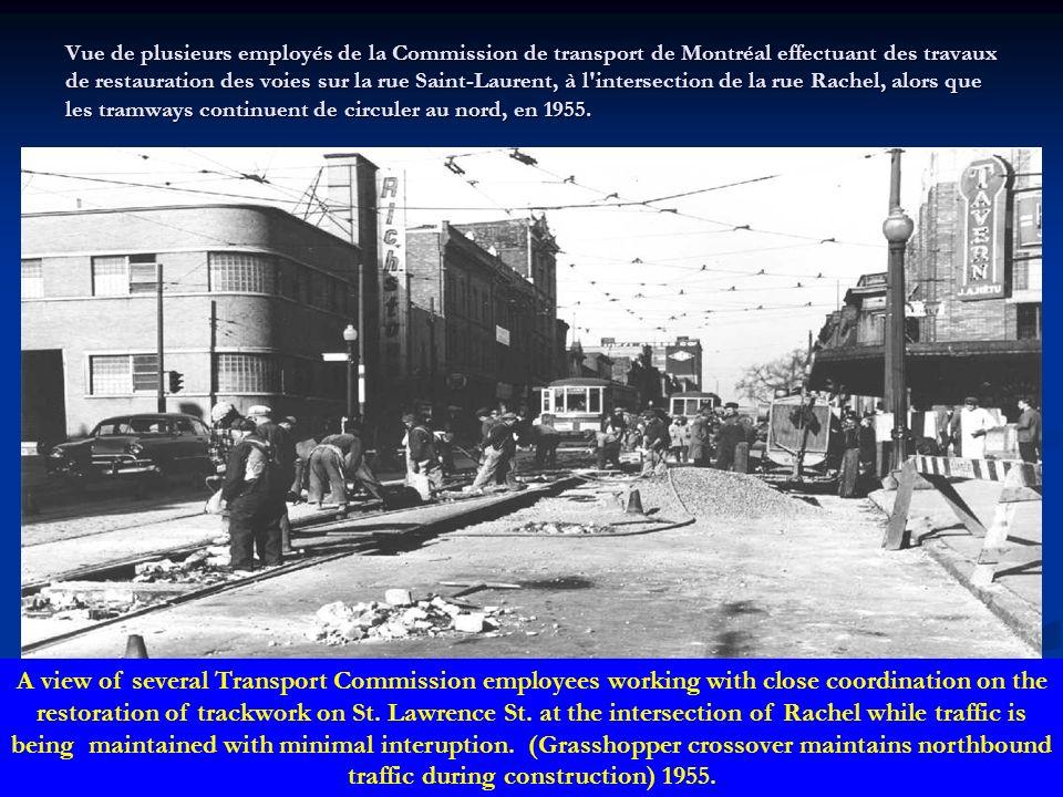 Vue des employés de la Commission de transport de Montréal occupés à retirer le filage électrique qui servait à la circulation des tramways sur la rue