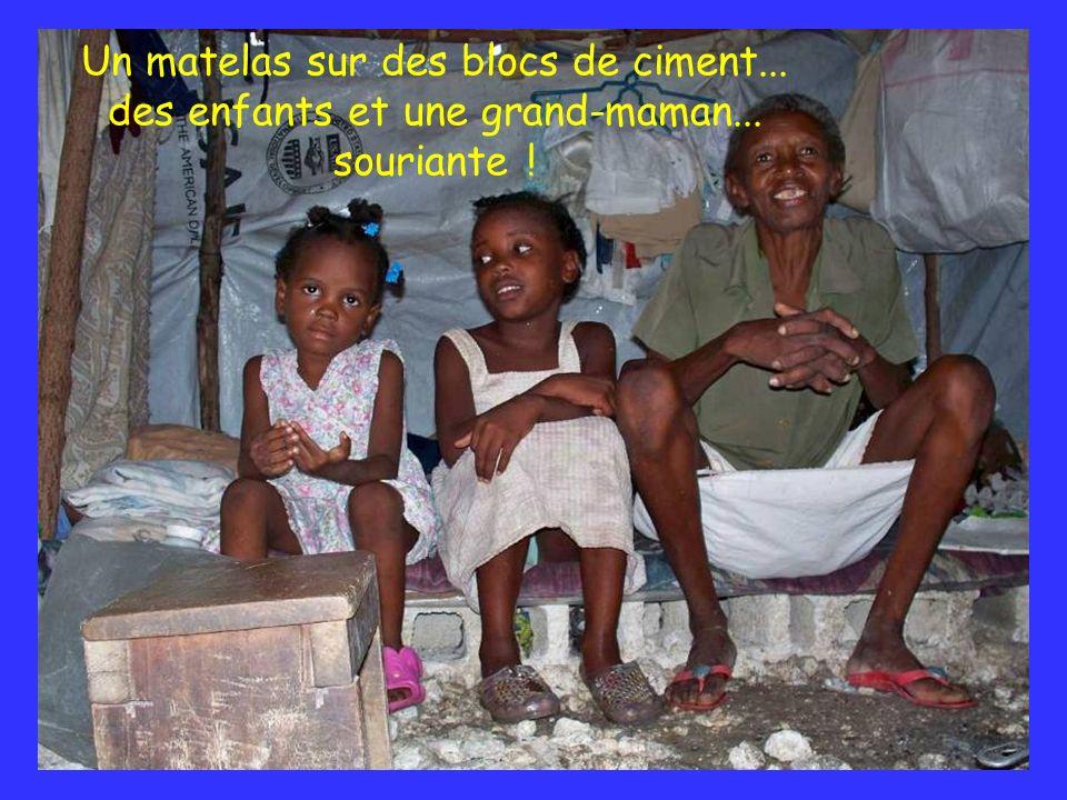 Un matelas sur des blocs de ciment... des enfants et une grand-maman... souriante !