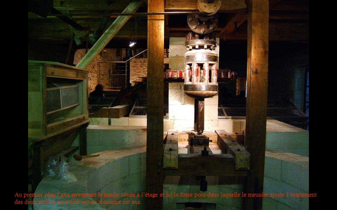Au premier plan laxe entraînant la meule située à létage et ici la fosse pour dans laquelle le meunier ajuste lécartement des deux meules en soulevant