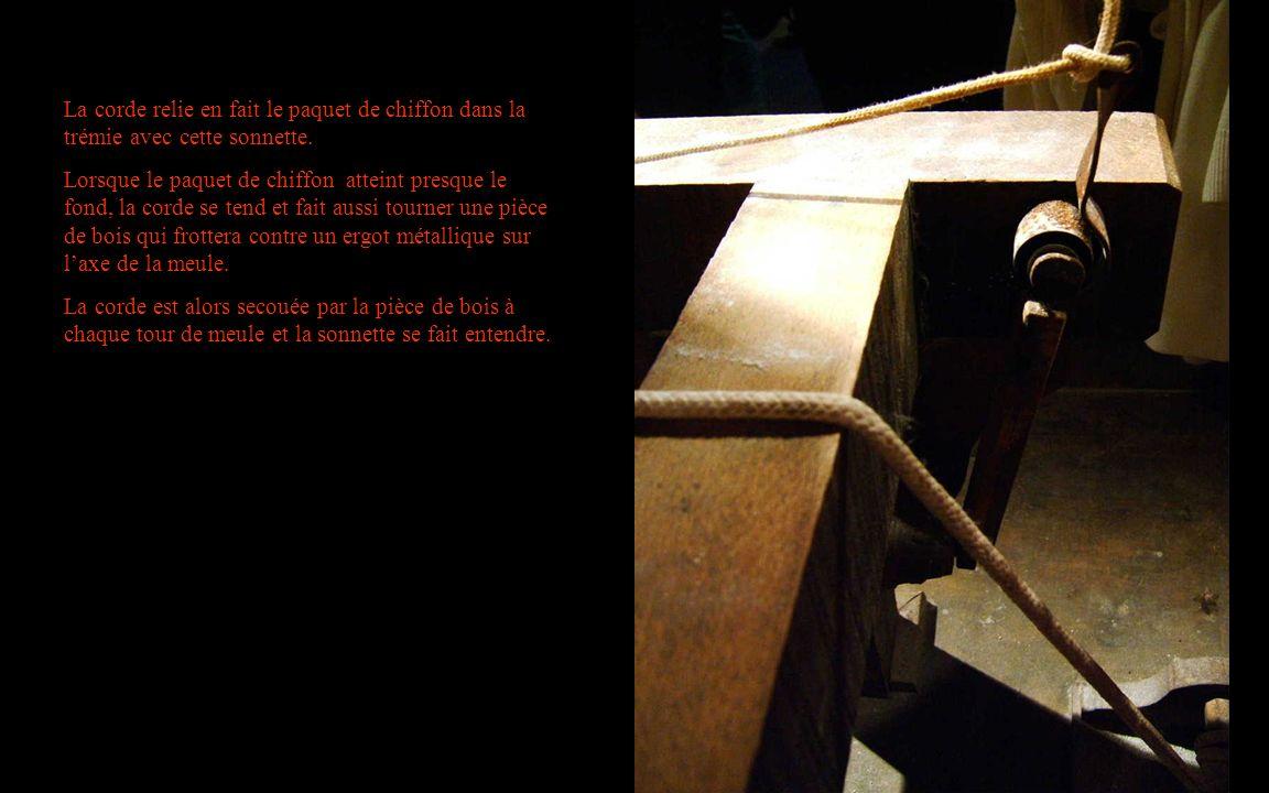 La corde relie en fait le paquet de chiffon dans la trémie avec cette sonnette. Lorsque le paquet de chiffon atteint presque le fond, la corde se tend
