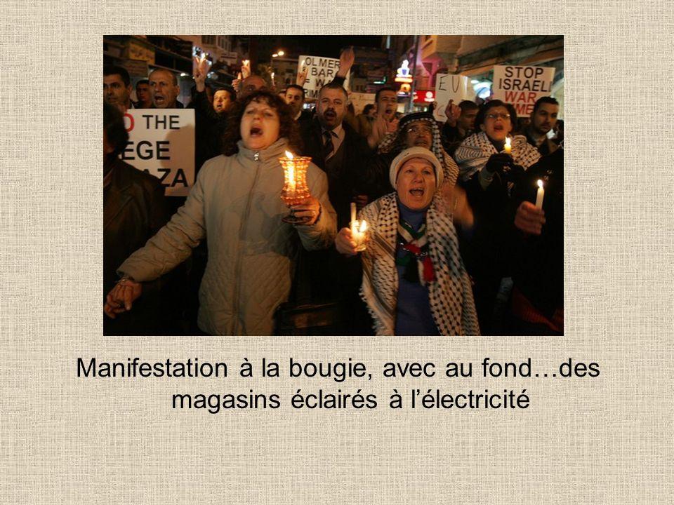 Manifestation à la bougie, avec au fond…des magasins éclairés à lélectricité