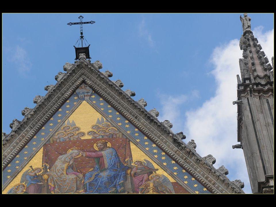 La façade consiste en un immense triptyque gothique doù ressortent des bas reliefs servant de base architecturale et des mosaïques dont les couleurs exaltent toute la façade