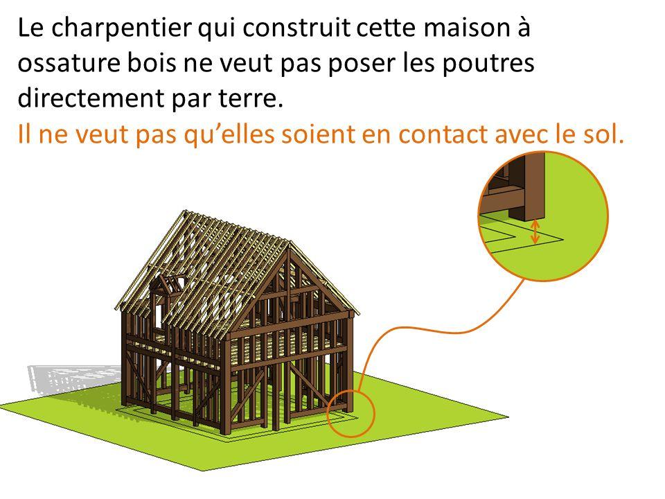 Le charpentier qui construit cette maison à ossature bois ne veut pas poser les poutres directement par terre. Il ne veut pas quelles soient en contac