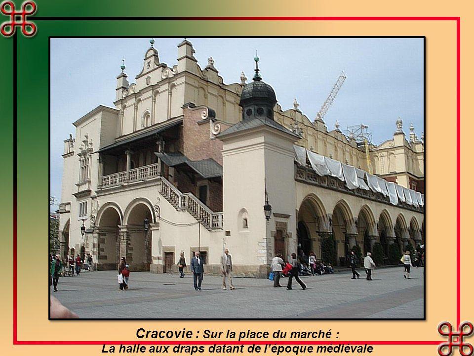 Cracovie. La place du marché, avec à sa droite lune des églises les plus connues de Pologne. Depuis 500 ans, chaque heure, depuis la plus haute tour,