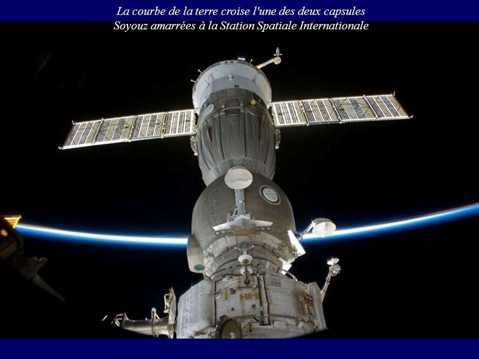 La courbe de la terre croise l'une des deux capsules Soyouz amarrées à la Station Spatiale Internationale