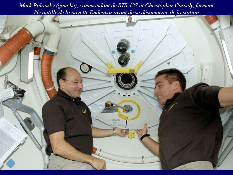 Mark Polansky (gauche), commandant de STS-127 et Christopher Cassidy, ferment l'écoutille de la navette Endeavor avant de se désamarrer de la station