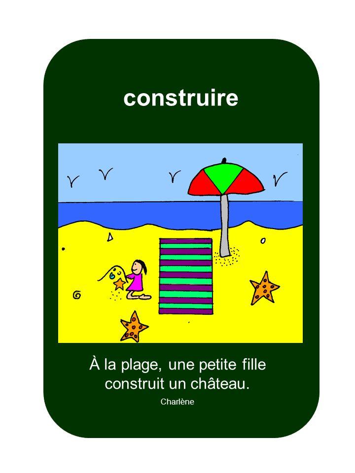 À la plage, une petite fille construit un château. Charlène construire