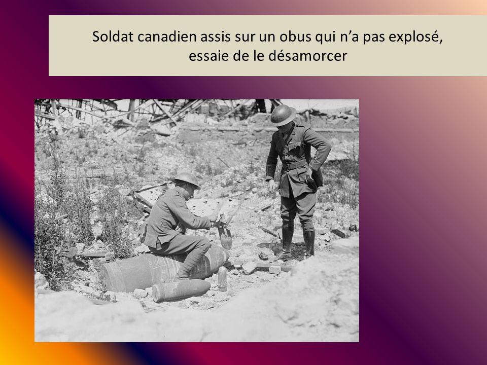 Soldat canadien assis sur un obus qui na pas explosé, essaie de le désamorcer
