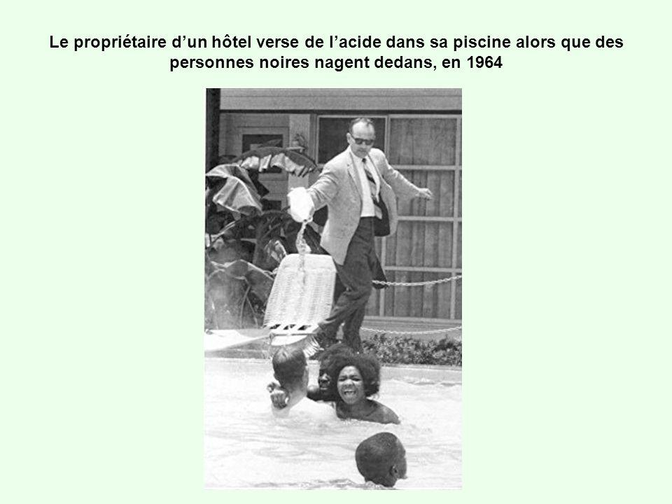 Le propriétaire dun hôtel verse de lacide dans sa piscine alors que des personnes noires nagent dedans, en 1964