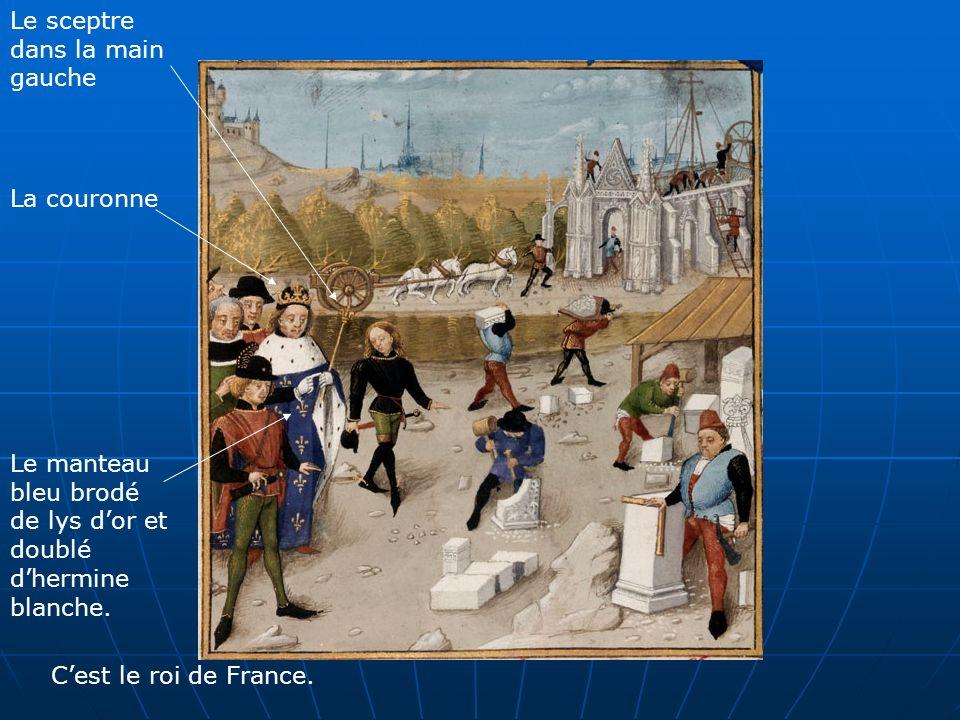 La couronne Le sceptre dans la main gauche Le manteau bleu brodé de lys dor et doublé dhermine blanche. Cest le roi de France.