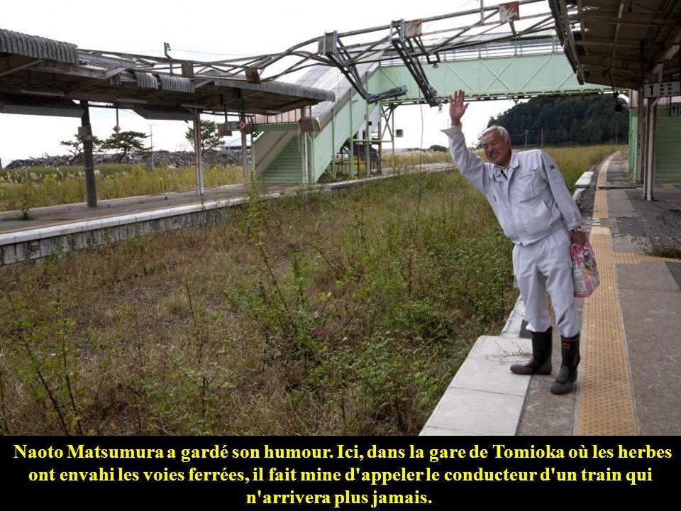 Naoto Matsumura dans la maison d'un de ses amis montre une photo du front de mer de Tomioka avant qu'il ne soit complètement détruit par le tsunami.