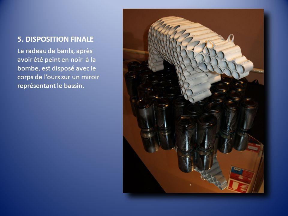 5. DISPOSITION FINALE Le radeau de barils, après avoir été peint en noir à la bombe, est disposé avec le corps de lours sur un miroir représentant le
