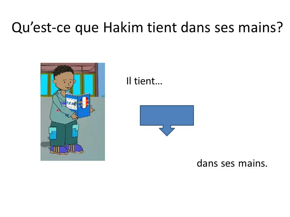Quest-ce que Hakim tient dans ses mains? Il tient… un livre. dans ses mains.