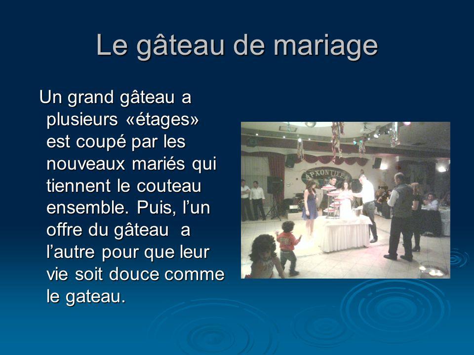 Le gâteau de mariage Un grand gâteau a plusieurs «étages» est coupé par les nouveaux mariés qui tiennent le couteau ensemble. Puis, lun offre du gâtea