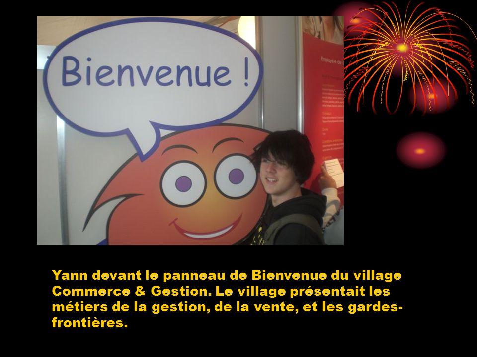Yann devant le panneau de Bienvenue du village Commerce & Gestion. Le village présentait les métiers de la gestion, de la vente, et les gardes- fronti