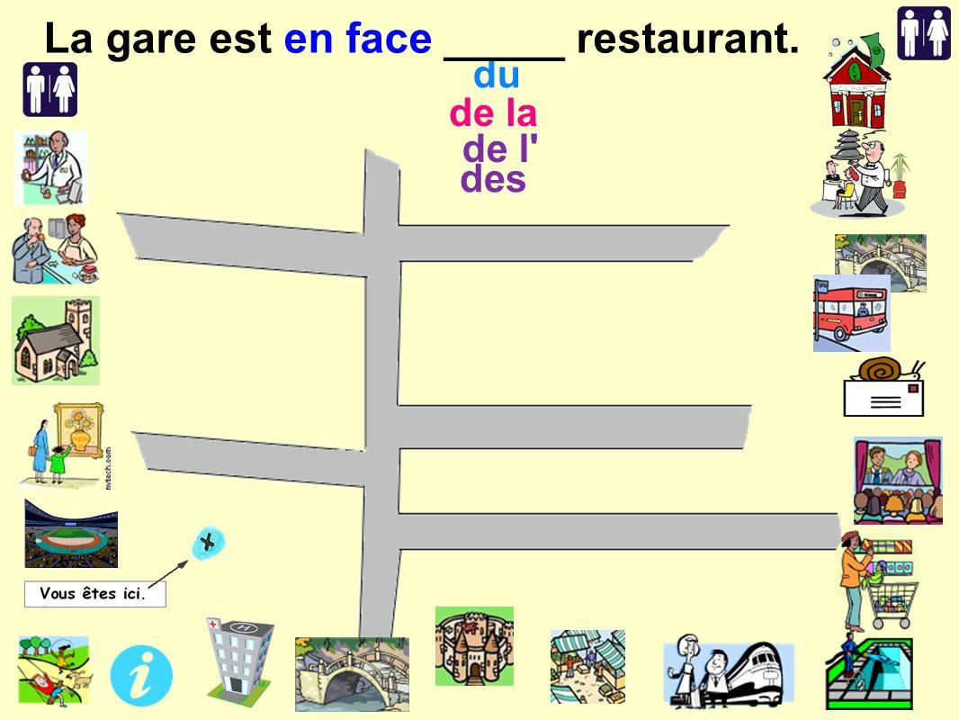 de l des de la du La gare est en face _____ restaurant.