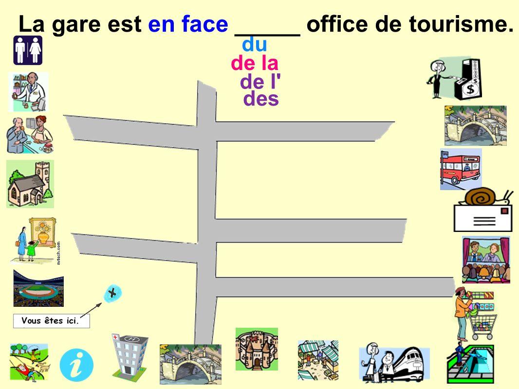 de l des de la du La gare est en face _____ office de tourisme.