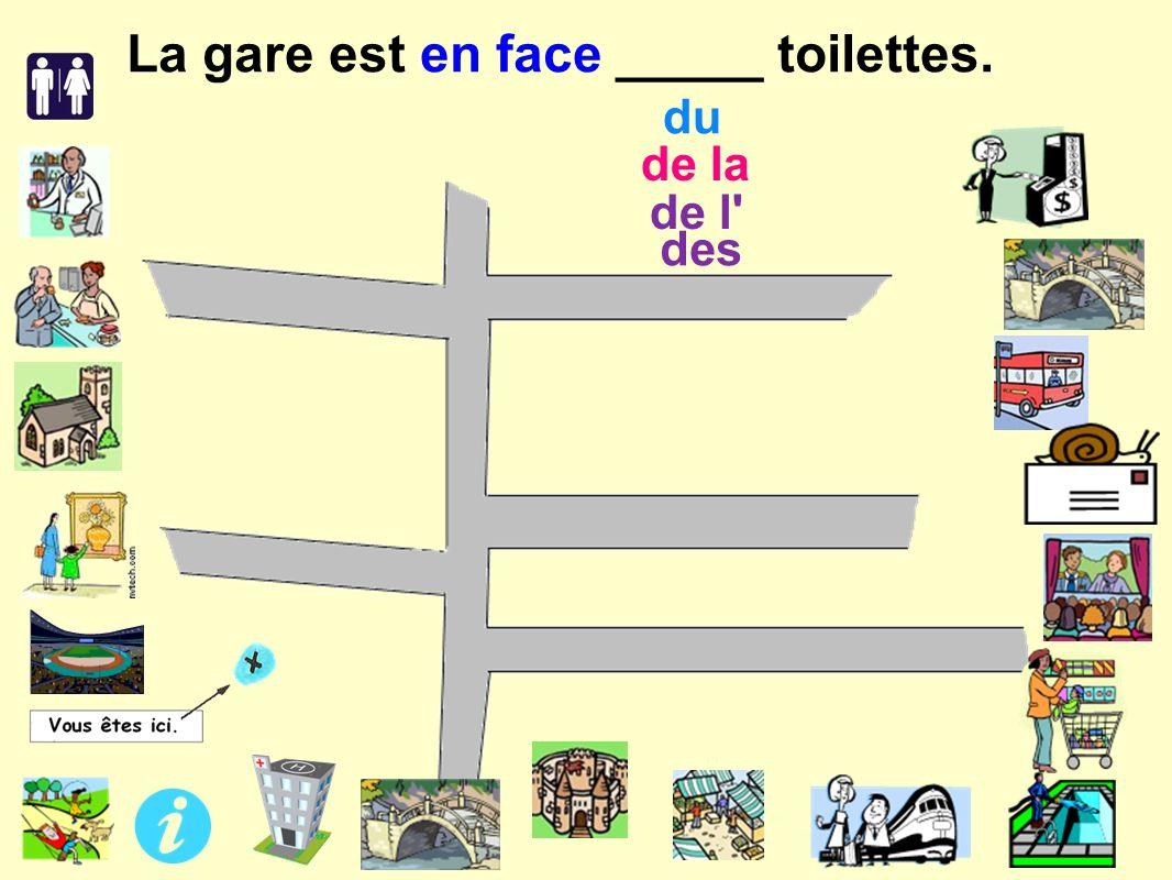 de l des de la du La gare est en face _____ toilettes.