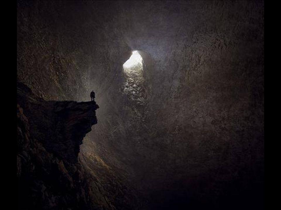 Un large rayon de soleil plonge dans la grotte comme une cascade. Au premier plan on peut voir une stalagmite qui ressemble à la patte d'un chien.