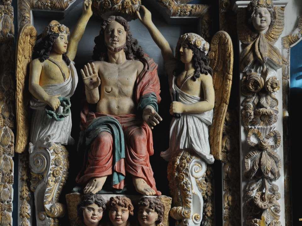 Le retable des Cinq Plaies (XVIIème siècle) : le panneau central présente le Christ res- suscité, assis et le torse dévê- tu, montrant ses plaies, alo