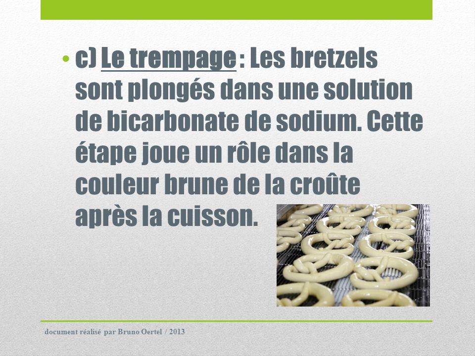 c) Le trempage : Les bretzels sont plongés dans une solution de bicarbonate de sodium. Cette étape joue un rôle dans la couleur brune de la croûte apr
