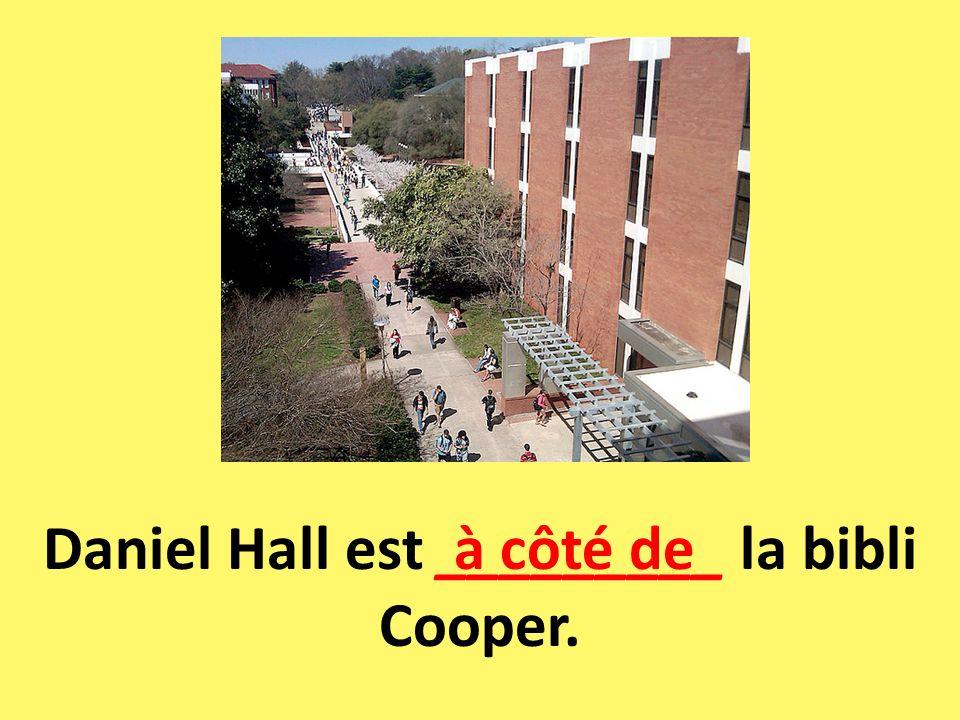 Daniel Hall est _________ la bibli Cooper. à côté de