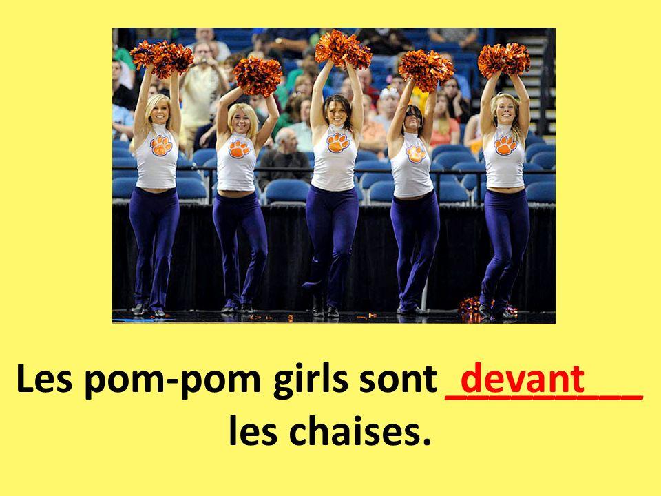 Les pom-pom girls sont _________ les chaises. devant