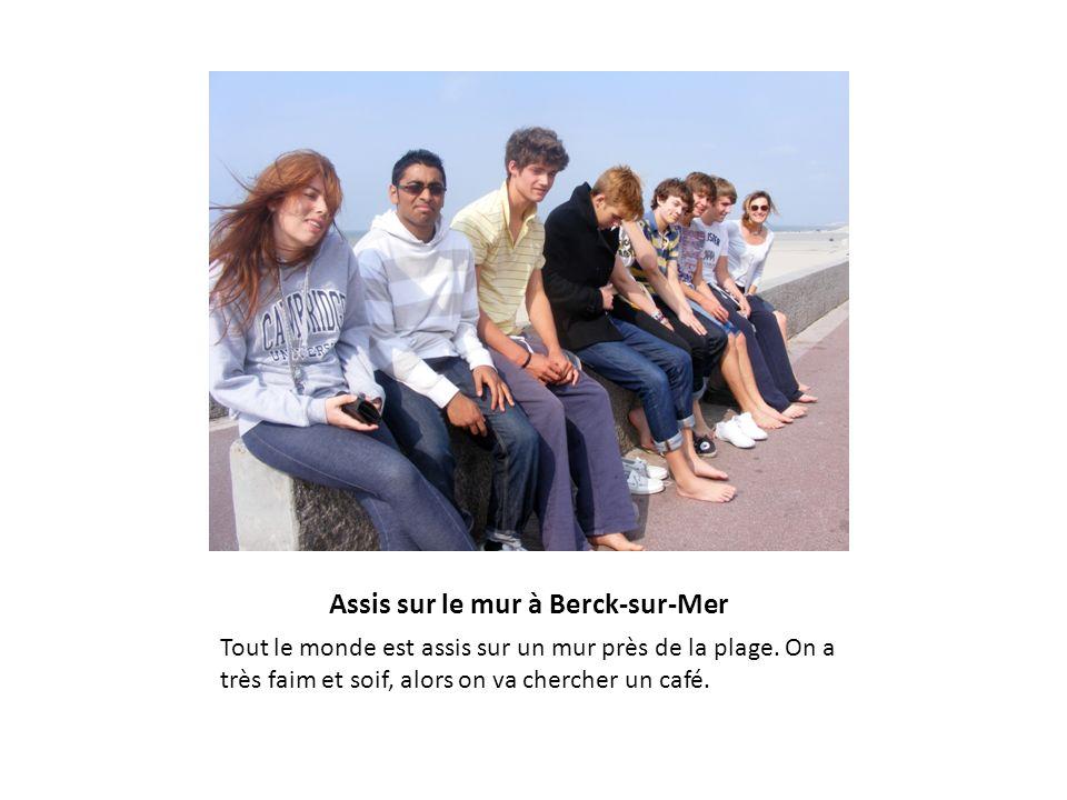 Assis sur le mur à Berck-sur-Mer Tout le monde est assis sur un mur près de la plage. On a très faim et soif, alors on va chercher un café.
