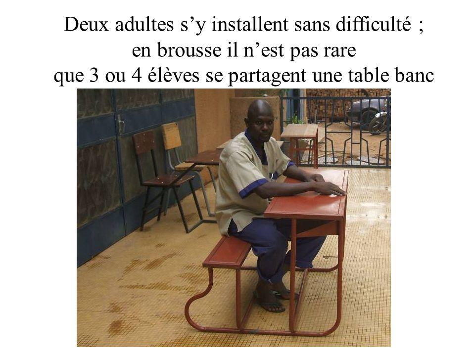 Deux adultes sy installent sans difficulté ; en brousse il nest pas rare que 3 ou 4 élèves se partagent une table banc