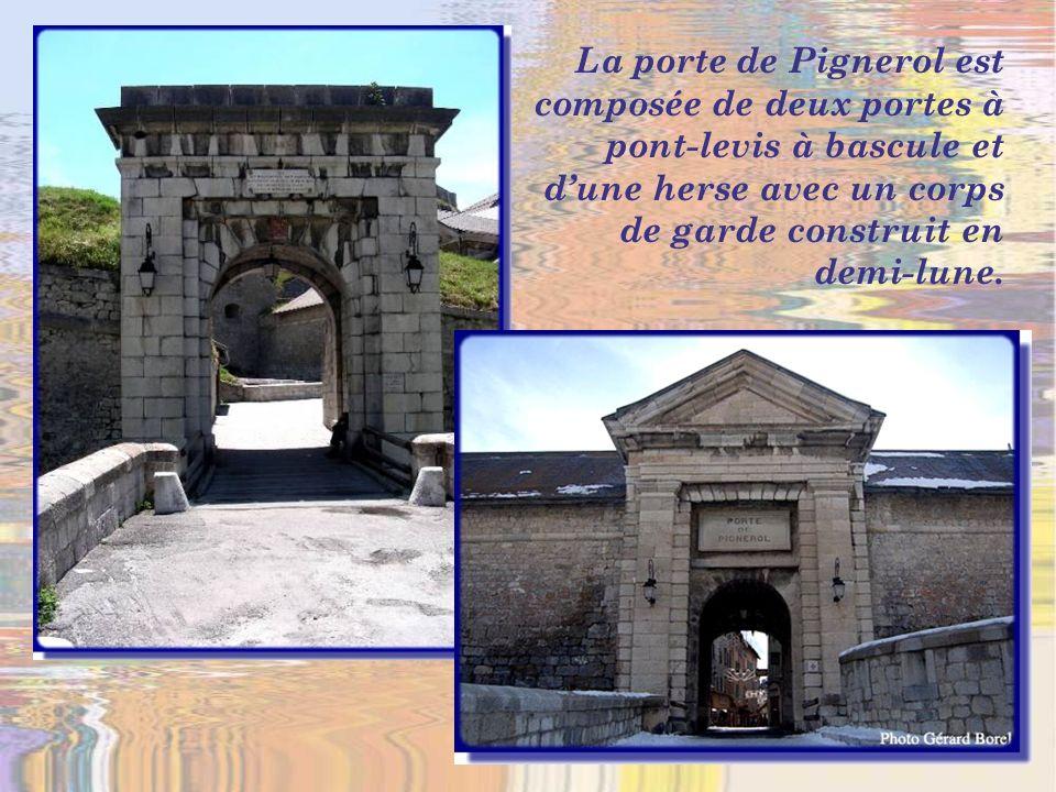 Des maisons hautes et colorées surplombent les murs denceinte et la porte dEmbrun…
