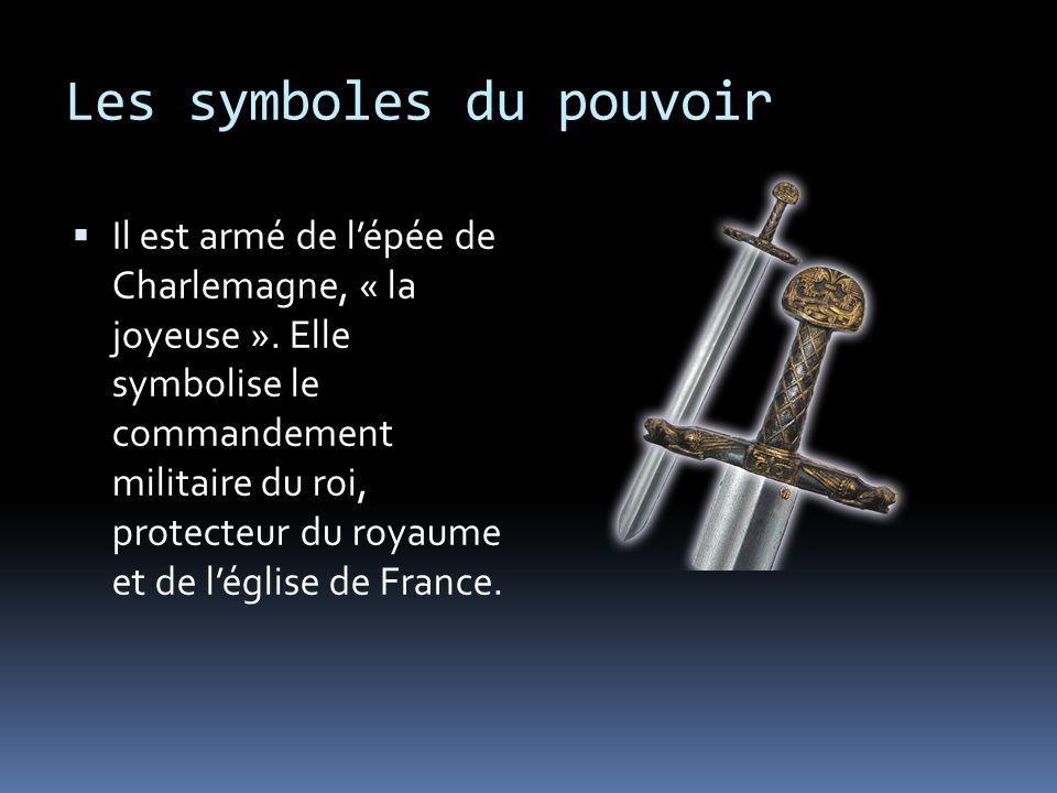 Les symboles du pouvoir Il est armé de lépée de Charlemagne, « la joyeuse ». Elle symbolise le commandement militaire du roi, protecteur du royaume et